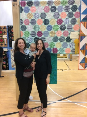 Grandma, Lucas and me in front of his baby quilt